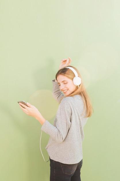 Jeune femme, écoute, musique, sur, casque, par, téléphone portable, danse, contre, vert, menthe, fond Photo gratuit