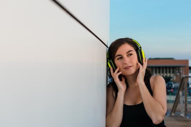 Jeune femme écoute de la musique avec ses écouteurs Photo Premium