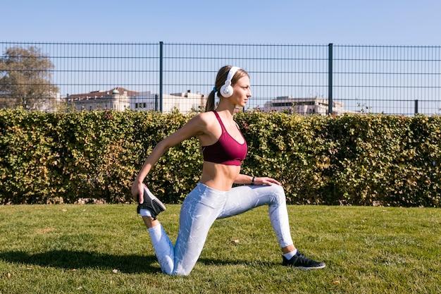 Jeune femme, écouter musique, sur, casque, étirer jambes, dans parc Photo gratuit