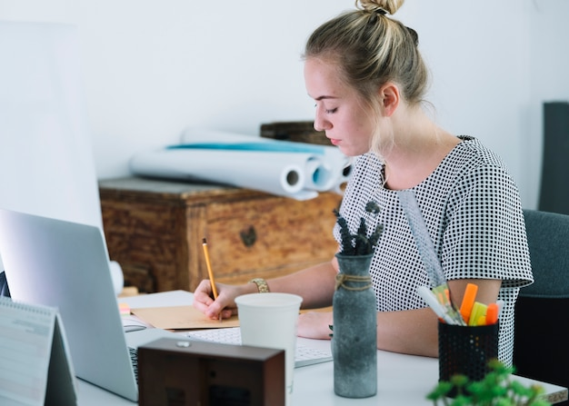 Jeune femme écrivant sur du papier sur le bureau Photo gratuit