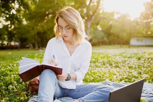 Jeune Femme écrivant Quelque Chose Dans Le Cahier Dans Le Parc Photo Premium
