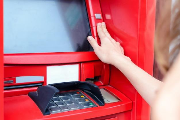 Jeune femme effectuant un paiement à un guichet automatique Photo Premium