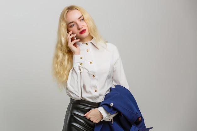 Jeune femme élégante, parler au téléphone portable sur fond blanc Photo Premium