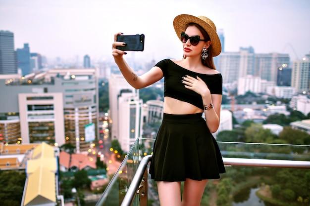 Jeune Femme élégante Portant Des Tenues D'été à La Mode à La Mode Faisant Selfie Touristique à La Terrasse De L'hôtel De Luxe Photo gratuit