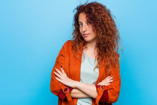 Jeune femme élégante, rousse, se sentant en confiance et se croisant les bras avec détermination. Photo Premium