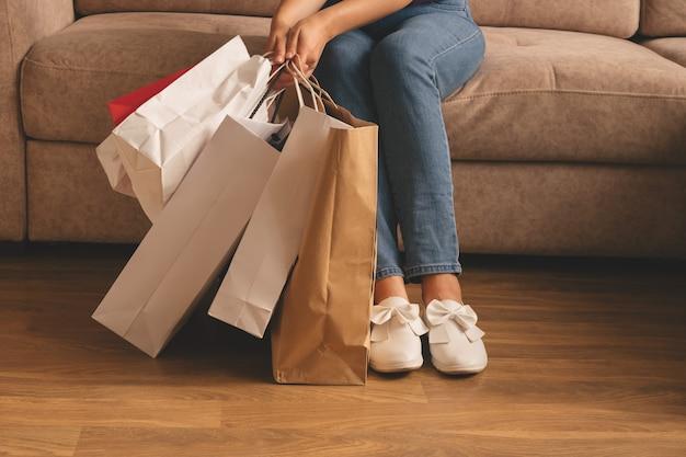 Jeune Femme élégante Tenant Des Sacs à Provisions Et Assis Sur Un Canapé Photo Premium