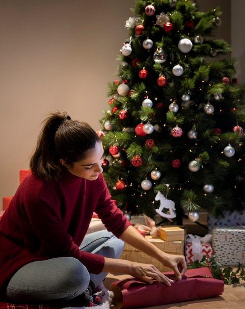 Jeune Femme Emballant Des Cadeaux Pour La Nuit De Noël Photo gratuit