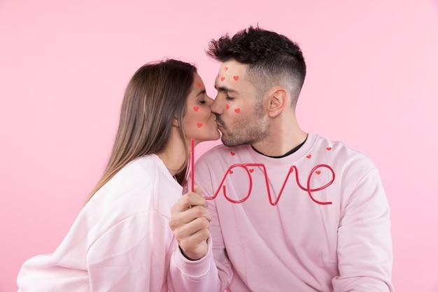 Jeune femme, embrasser, homme, à, coeurs papier, sur, faces, et, signe amour Photo gratuit