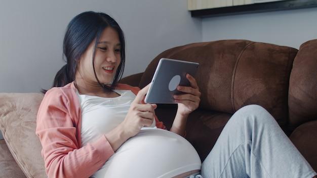 Jeune femme enceinte asiatique à l'aide de la tablette recherche des informations sur la grossesse. maman se sentant heureuse, souriante, positive et paisible tout en prenant soin de son enfant allongé sur un canapé dans le salon à la maison. Photo gratuit