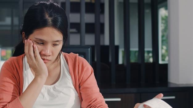 Jeune femme enceinte asiatique répertorie les revenus et les dépenses à la maison. maman inquiète, sérieuse, stressée tout en enregistrant un budget, une taxe, un document financier dans le salon à la maison. Photo gratuit