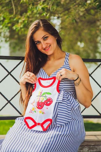 Jeune femme enceinte attrayante. femme enceinte tenant un corps de bébé. concept de mode de vie de ville. Photo Premium