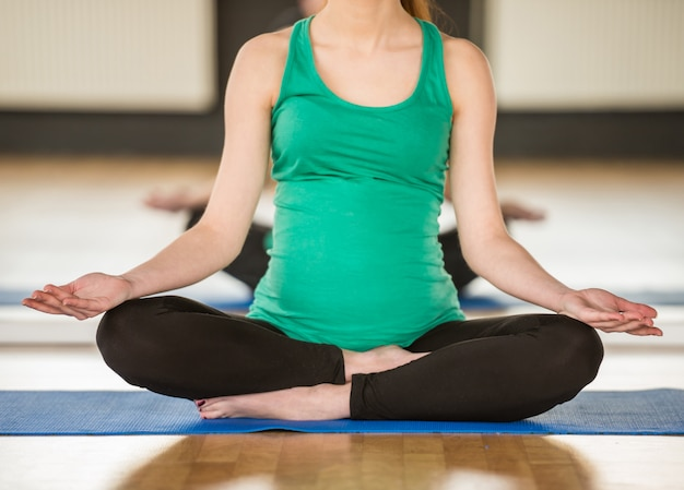 Jeune femme enceinte fait du yoga. Photo Premium