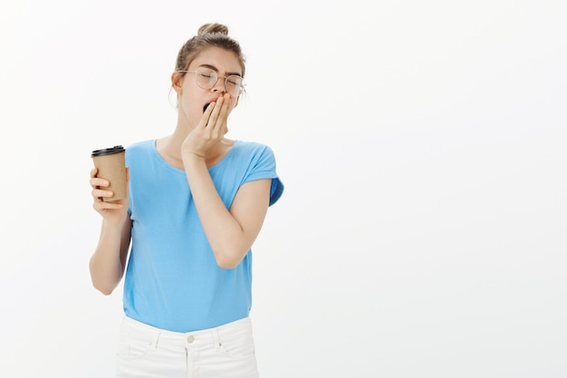 Jeune Femme Endormie Dans Des Verres, Boire Du Café Et Bâiller, Tasse De Caféine Du Matin Photo gratuit