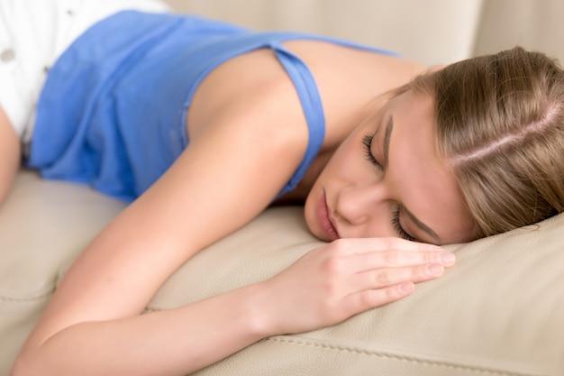 Jeune femme endormie privée allongée endormie sur le canapé, gros plan Photo gratuit