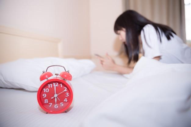 Jeune femme endormie et réveil dans la chambre à la maison Photo gratuit