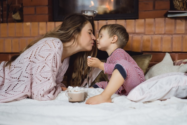 Jeune femme avec un enfant au coin du feu. mère et fils boivent du cacao avec des guimauves Photo gratuit