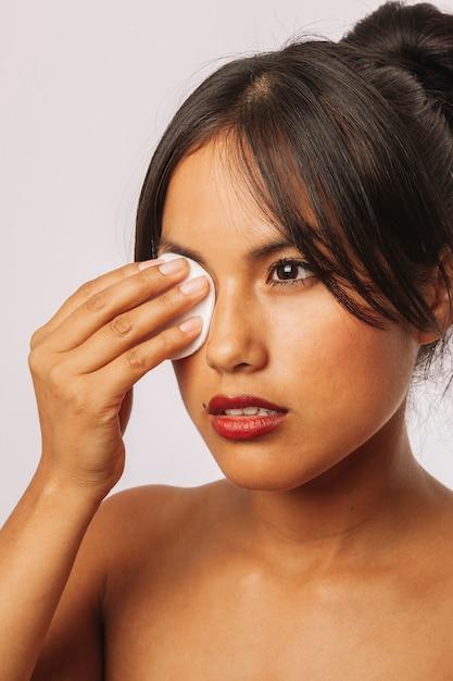 Jeune femme enlève le maquillage des yeux Photo gratuit