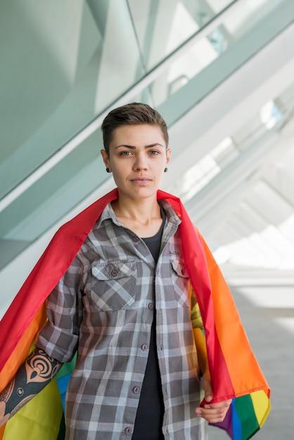 Jeune femme enveloppée dans le drapeau arc-en-ciel Photo gratuit