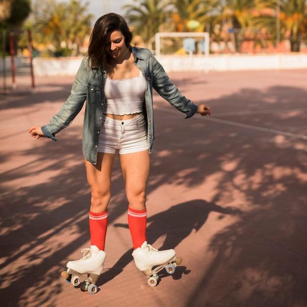 Jeune femme en équilibre sur le patin à roulettes Photo gratuit