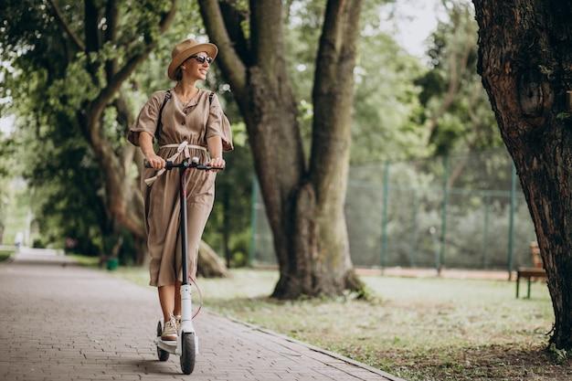 Jeune Femme, équitation, Scooter, Dans Parc Photo gratuit