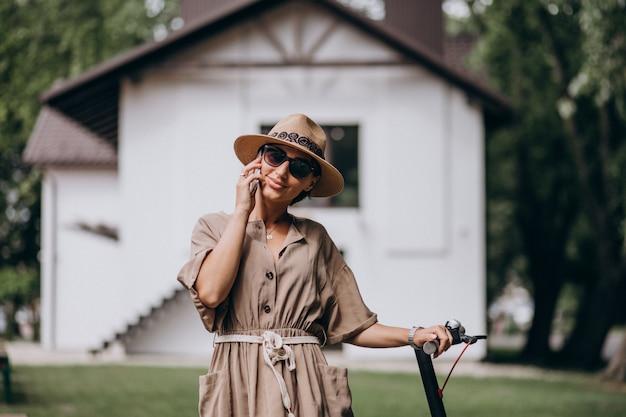 Jeune femme, équitation, scooter, parler, téléphone, dans, parc Photo gratuit