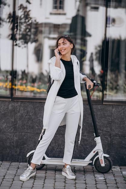 Jeune femme, équitation, scotter, en ville, utilisation, téléphone Photo gratuit