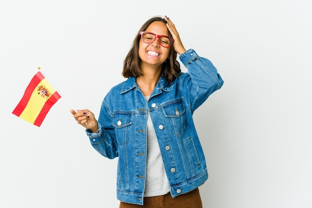 Jeune Femme Espagnole Tenant Un Drapeau Isolé Sur Fond Blanc Rit Joyeusement En Gardant Les Mains Sur La Tête. Photo Premium