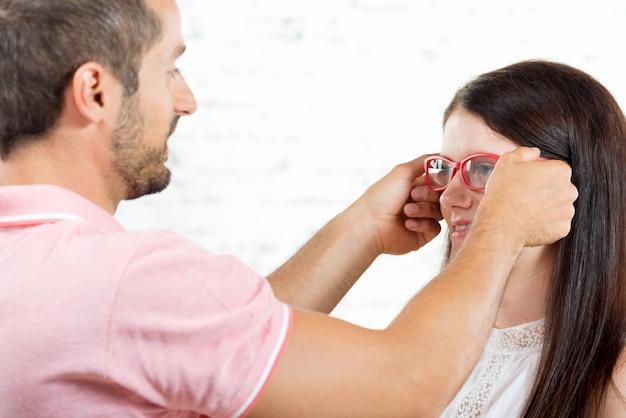 Jeune femme essaye des lunettes à l'opticien Photo Premium