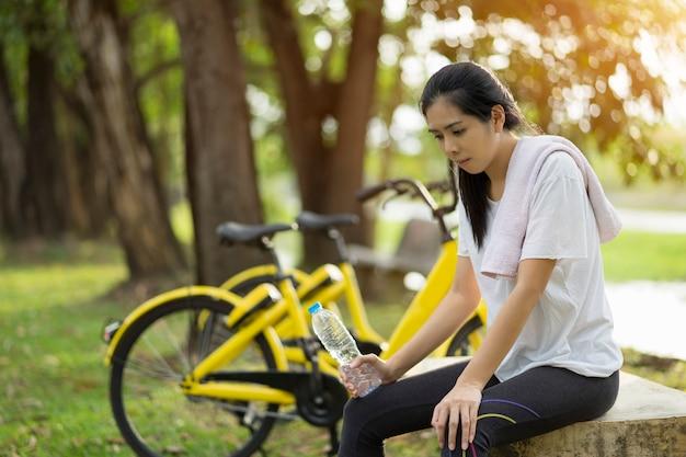 Une jeune femme a essayé de s'entraîner et de tenir une bouteille d'eau, se reposant à la fin de l'exercice au jardin, healthy concept. Photo Premium