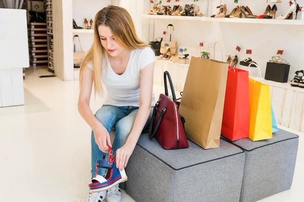 Jeune femme, essayer, chaussures, dans, magasin chaussure Photo gratuit