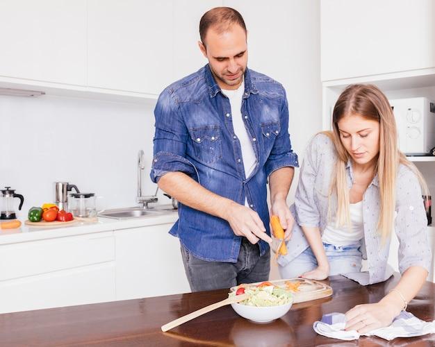 Jeune Femme Essuyant La Table Avec Une Serviette Et Son Mari Préparant La Salade Dans La Cuisine Photo gratuit
