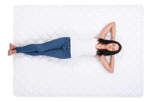 Jeune femme est allongée sur le lit et se repose. Photo Premium