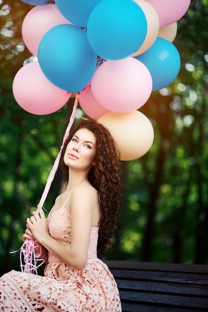 Jeune Femme Est Assise Dans Le Parc Sur Un Banc Et Détient Des Ballons Multicolores Dans Les Mains Photo Premium