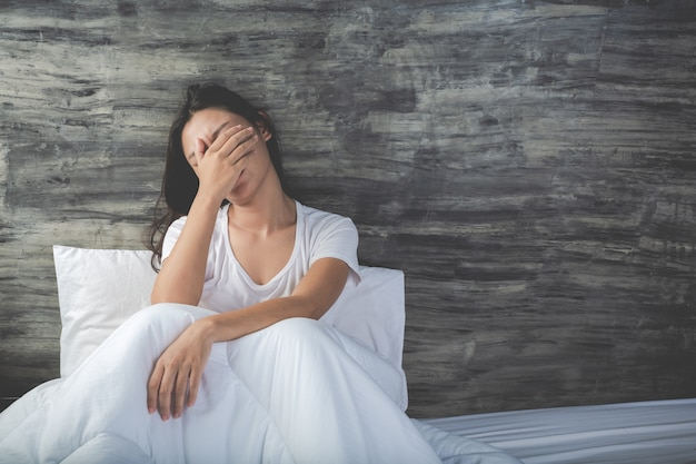 Jeune femme est déprimée sur un lit blanc Photo gratuit