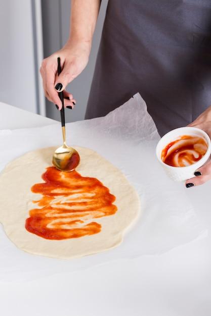 Jeune femme étalant la sauce tomate sur la pâte sur du papier sulfurisé Photo gratuit