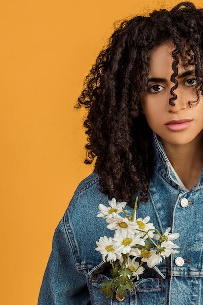 Jeune femme ethnique avec des fleurs sur une veste en jean Photo gratuit