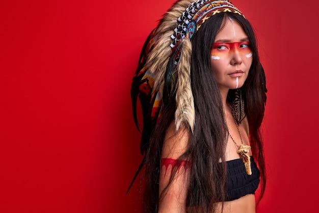 Jeune Femme Ethnique Avec Gardon Sur Sa Tête Isolé Sur Mur Rouge, Femme En Haut, Chaman Photo Premium