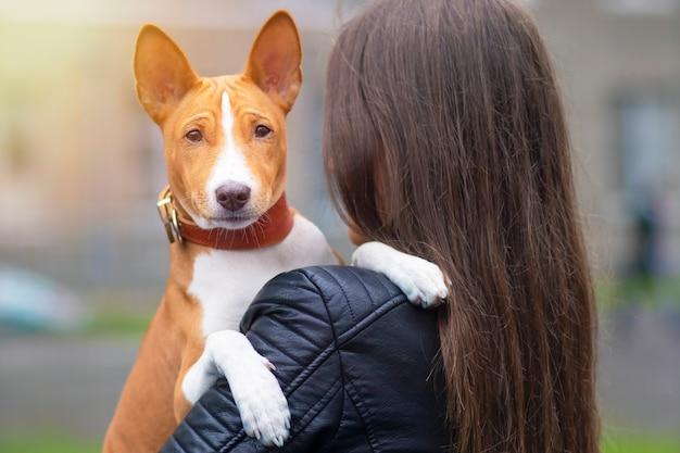 Jeune Femme étreint Son Chien Basenji Terrier Photo Premium
