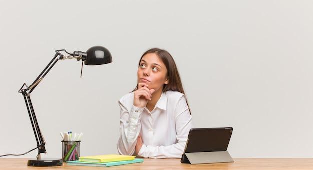 Jeune femme étudiante travaillant sur son bureau, doutant et confus Photo Premium