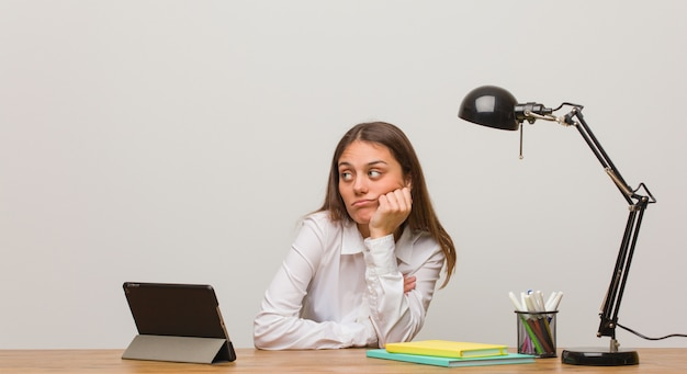 Jeune femme étudiante travaillant sur son bureau en train de penser à quelque chose, regardant de côté Photo Premium