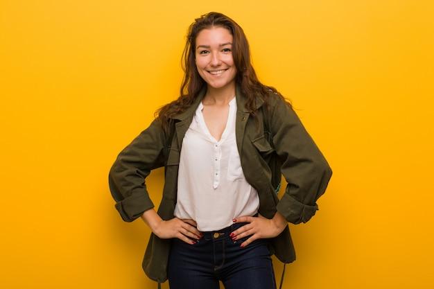 Jeune femme européenne confiante en gardant les mains sur ses hanches. Photo Premium