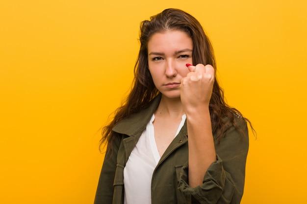 Jeune femme européenne isolée sur fond jaune montrant le poing à la caméra, expression faciale agressive. Photo Premium