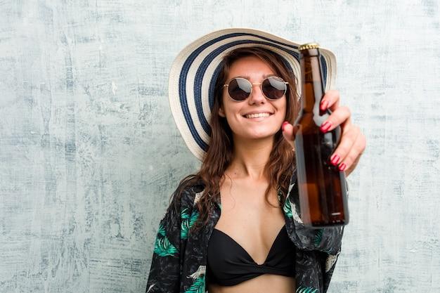 Jeune femme européenne portant un bikini et buvant une bière Photo Premium