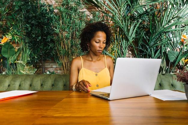 Jeune femme, examiner, document, à, ordinateur portable, sur, table bois Photo gratuit