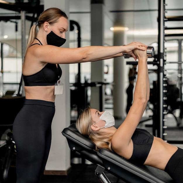 Jeune Femme Exerçant Au Gymnase Et Portant Un Masque Photo gratuit