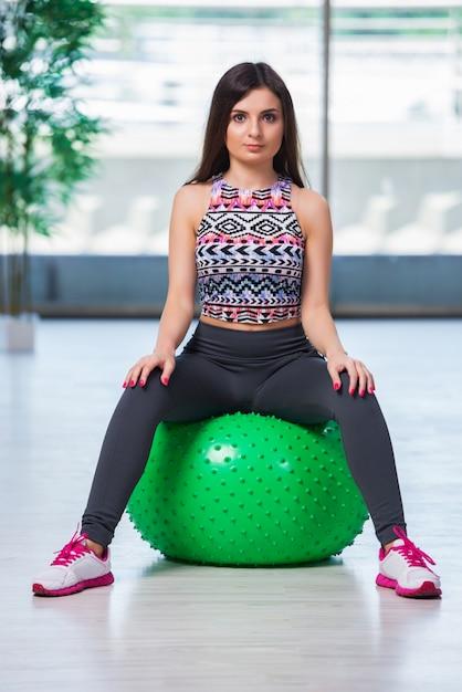 Jeune femme exerçant avec swiss ball dans le concept de santé Photo Premium