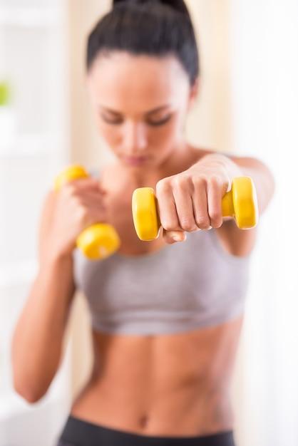 Jeune femme exerce avec des haltères à la maison. Photo Premium