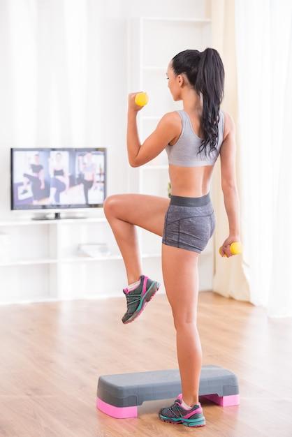Jeune femme exerce avec des haltères et pas à la maison. Photo Premium