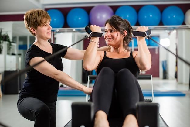 Jeune femme, exercice, sur, pilates, appareil, reformer, à, instructeur, à, gymnase Photo Premium