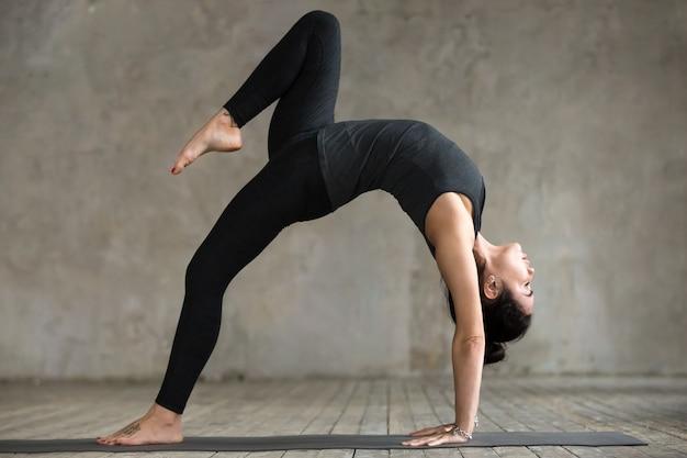 Jeune femme, faire, une jambe, roue, poser, exercice Photo gratuit